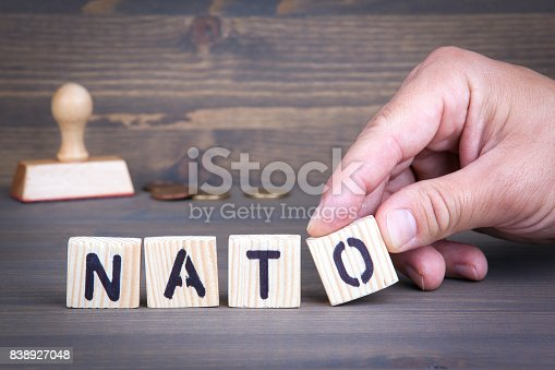 istock Nato from wooden letters on wooden background 838927048