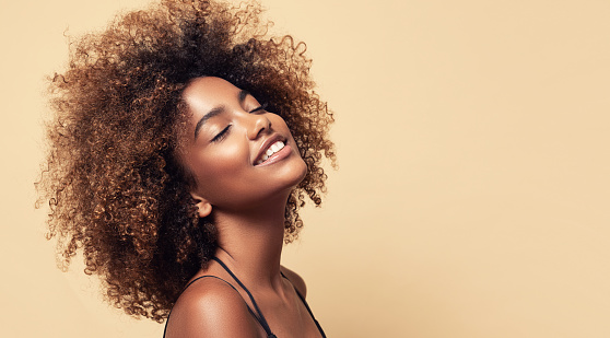 Gladness on the face of perfectly looking brown skinned young woman.. Natural, dense afro hair on the head of young beautiful model, white toothy smile on her face. Girl with vibrant, melanin-rich skin tone.