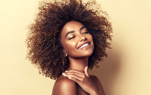 Portrait of perfectly looking brown haired young woman. Natural, dense afro hair on the head of young beautiful model, white toothy smile on her face. Girl with vibrant, melanin-rich skin tone. Closed eyes and happy smile.