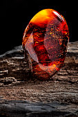 A piece of dark red semi transparent natural amber, classification color cherry or dragon blood, has cracks on its surface. Polished, oval shape. Placed on dark stoned wood texture.