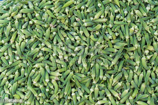 In natural and organic farmer's market, okra vegetables are stacked in a surface as background.