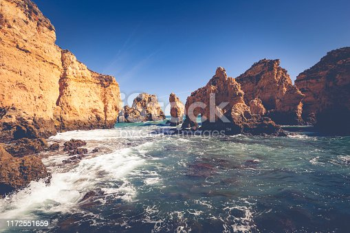 natural arch coastal cliffs (ponta da piedade) near lagos village in portugal.