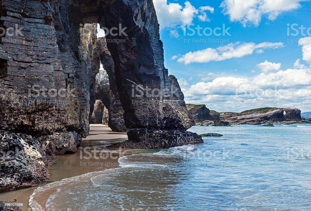 Natural arches on beach. - Photo