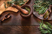 High angle view of natural aromatic herbs like dill, thyme, oregano and rosemary on wooden mortar and over dark brown wooden table. Predominant colors are brown and green. copy space on the lower part of the image. Low key DSLR photo taken with Canon EOS 6D Mark II and Canon EF 24-105 mm f/4L