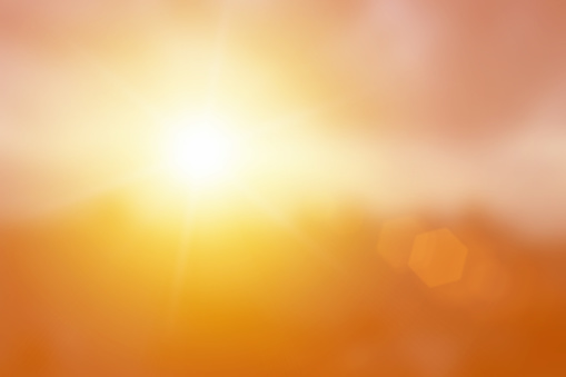 Natural background blurring warm colors and bright glod sunlight. Bokeh or Christmas background Green Energy at sky sunny color orange light patterns plain abstract flare evening clouds blur.
