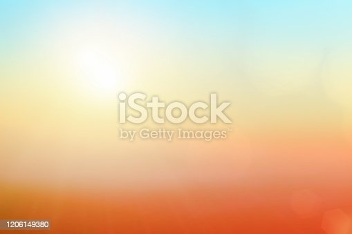 Natural background blurring warm colors and bright sun light. Bokeh or Christmas background Green Energy at sky sunny color orange light patterns plain abstract flare evening clouds blur.