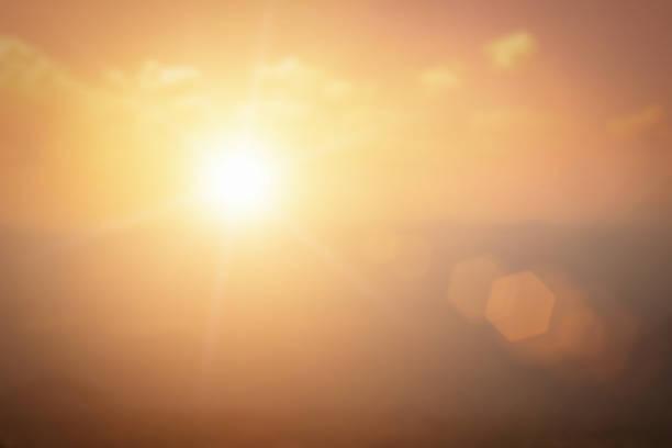 fundo natural desfocando cores quentes e luz solar brilhante. bokeh ou fundo natalino energia verde no céu cinza cor laranja padrões de luz simples abstrato flare nuvens à noite embaçam. - sol nascente horizonte drone cidade - fotografias e filmes do acervo