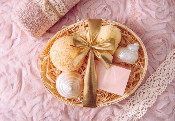 natuurlijke bamboe materiaal giftmand die met versnipperd houten excelsior met diverse spa badkamersproducten, roze zeepstaaf, badbom, natuurlijke spons op uitstekende licht roze achtergrond wordt gevuld. schoonheid aanwezig. - pink and orange seashell background stockfoto's en -beelden