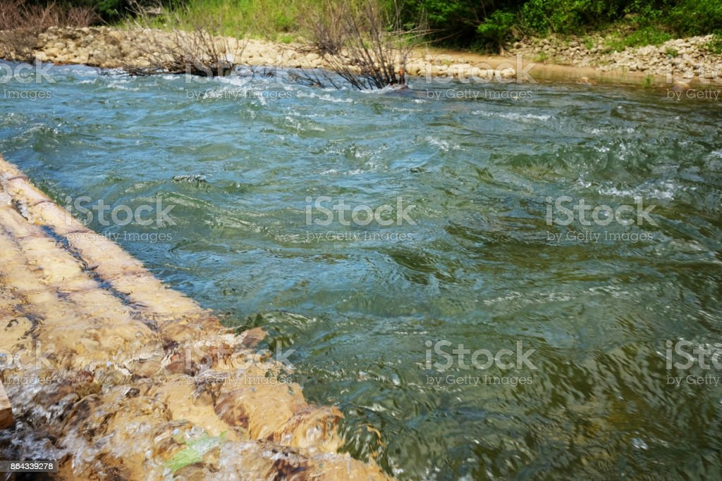 Natural bamboo raft floating on water in river. stock photo
