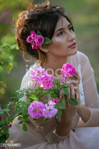1054970060 istock photo Natural beauty girl closeup portrait of a girl with wild rose branches 1210134621