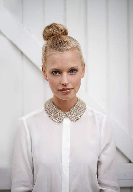 Natural beauty Cropped shot of a pretty blonde standing in front of a wooden door blouse stock pictures, royalty-free photos & images