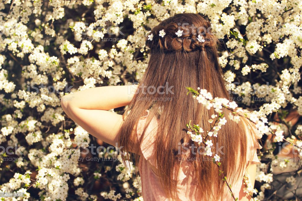 Natural Beauty Portrait Of Beautiful And Young Longhaired Girl Correcting Her Flowers Standing Back To Camera On Flower Background Stock Photo Download Image Now Istock
