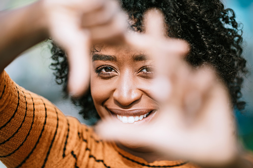 A beautiful African American woman smiles while framing her face with her fingers.  Shot in Los Angeles, California.