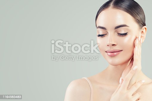 istock Natural beauty portrait. Young beautiful model woman with clear skin. Skin care and facial treatment concept 1164583483