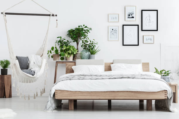 Natural bedroom with plants Plants behind wooden bed near hammock with pillows in natural bedroom with posters on white wall bed furniture stock pictures, royalty-free photos & images