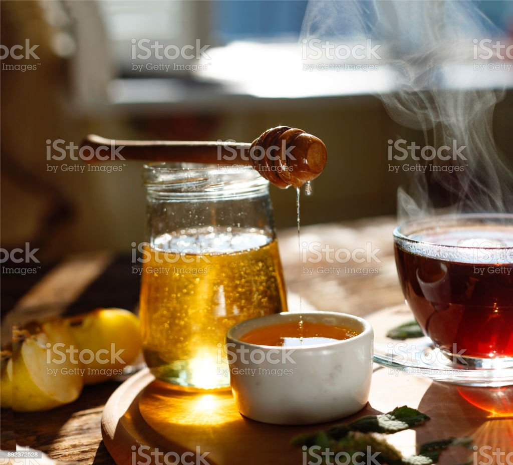 Natural bee honey with morning tea. Pouring honey. stock photo