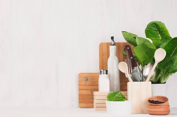 natürliche beige- und brauntönen hölzerne küchenutensilien und grüne pflanze licht weiße holz hintergrund, textfreiraum. - küche deko grün stock-fotos und bilder