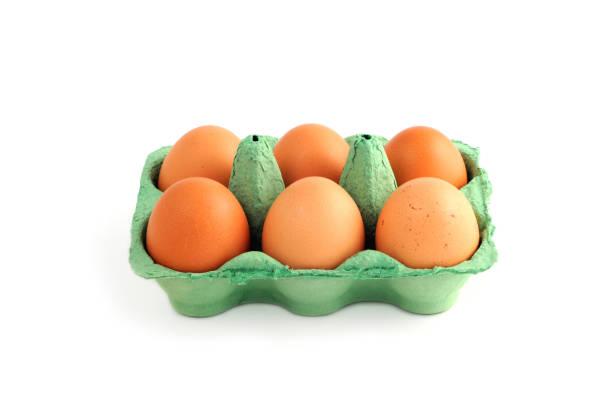 natuurlijke beige eieren in een doos op witte geïsoleerde achtergrond. - chicken bird in box stockfoto's en -beelden