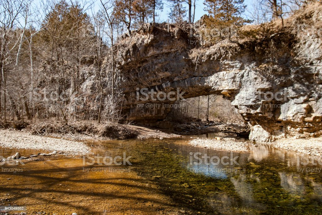 Natural Bridge crosses Clifty Creek in the backwoods of Missouri is serene and beautiful stock photo