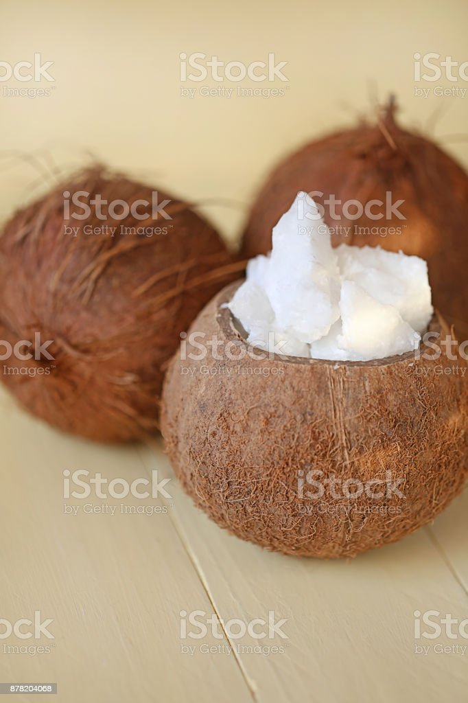 Natural coconut oil. Coconut in a cut and coconut oil in a brown wooden cup on a yellow wooden board background stock photo
