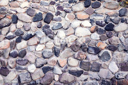 istock Natural colorful pebbles wall on beach in summer 1126924666