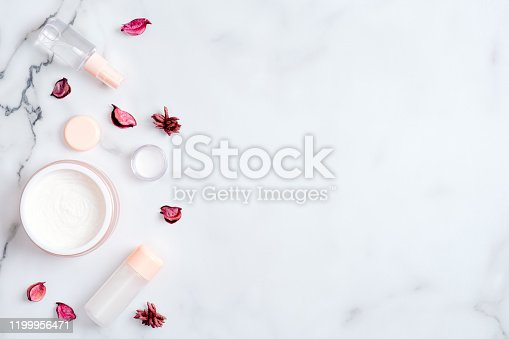 1128479585 istock photo Natural cosmetic cream and lotion bottle with pink flower petal on marble table. Beauty organic product. Flat lay, top view, copy space. Skincare and body care concept 1199956471