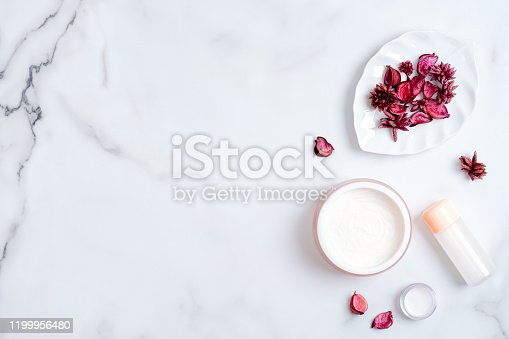 1128479585 istock photo Natural cosmetic cream and lotion bottle with pink flower petal on marble table. Beauty organic product. Flat lay, top view, copy space. Skincare and body care concept 1199956480