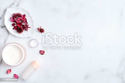 1128479585 istock photo Natural cosmetic cream and lotion on marble background with red flower petals. Beauty organic product. Top view, flat lay, copy space. Skincare and body care concept 1199956494