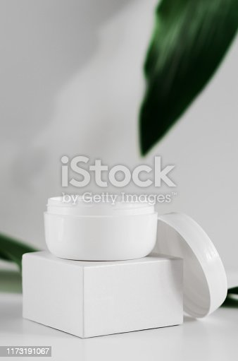istock Natural cosmetic cream jar and greenery side view. Opened white plastic container and blurred plant leaves on background. Organic cosmetology creative concept. Skin care, hygiene accessory 1173191067