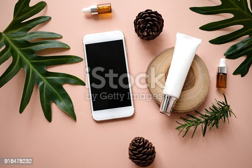 istock natural cosmetic cream , serum, skincare blank bottle packaging with leaves herb, wood . bio organic product.beauty and spa concept. online shopping with mobile phone and credit card. 918478232