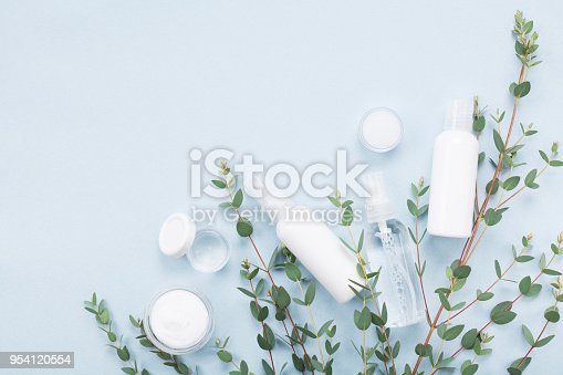 istock Natural cosmetic for spa and body care decorated eucalyptus leaves on blue table top view. Flat lay. 954120554