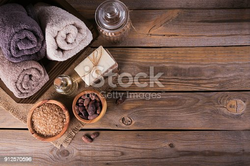 istock Natural cosmetic oil, sea salt and natural handmade soap with cocoa beans on rustic wooden background 912570596