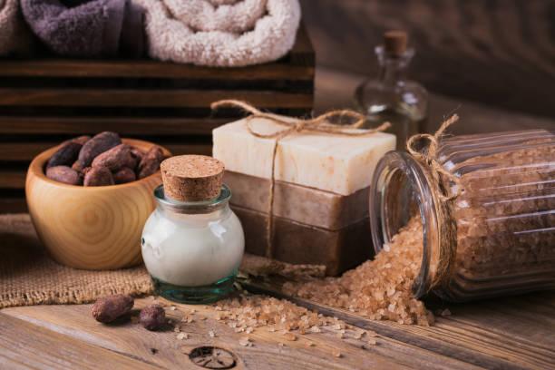 natürliche kosmetik öl, meer salz und natürliche handgemachte seife mit kakaobohnen auf rustikalen hölzernen hintergrund - makeup selbst gemacht stock-fotos und bilder