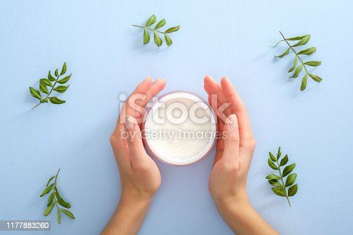 1151624350istockphoto Natural cosmetic skincare moisturizer cream in jar and female hands over blue background decorated eucalyptus leaves. Flat lay, top view, overhead. Skin care, beauty and healthcare concept. 1177883260