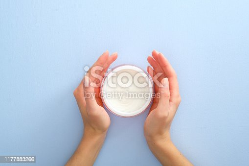1151624350istockphoto Natural cosmetic skincare moisturizer cream in jar and female hands over pastel blue background. Flat lay, top view, overhead. Skin care, beauty and healthcare concept. 1177883266