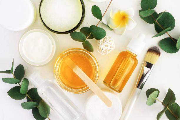 ingredientes de cosméticos naturais para o cuidado de pele, corpo e cabelo. mel no frasco e verde, folhas de eucalipto de ervas. - condição natural - fotografias e filmes do acervo