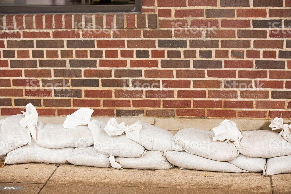 Natural disasters. Flooding. Sandbags line building wall. stock photo