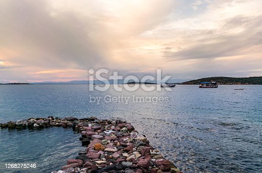 A road made of stones with sea, sky and fishing boats in the background.