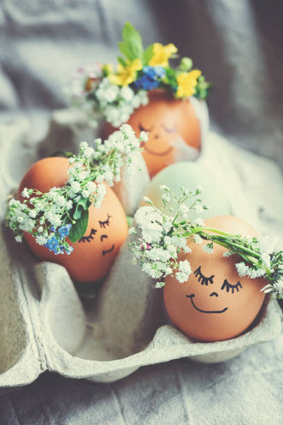Natural easter eggs with funny painted face and sweet flower wreath stock photo