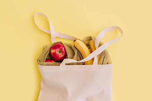 istock Natural eco bag with fruits on yellow background. Zero waste shopping and plastic free concept. 1140316233