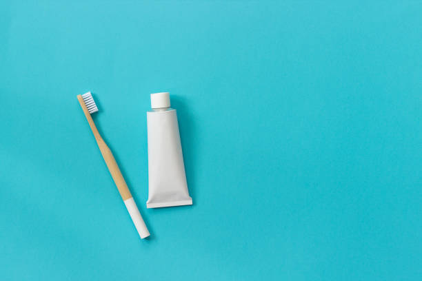 Natural eco-friendly bamboo brush with white bristles and tube of toothpaste. Set for washing on paper blue background. Copy space for text or your design Top view Flat lay Natural eco-friendly bamboo brush with white bristles and tube of toothpaste. Set for washing on paper blue background. Copy space for text or your design Top view Flat lay. toothbrush stock pictures, royalty-free photos & images