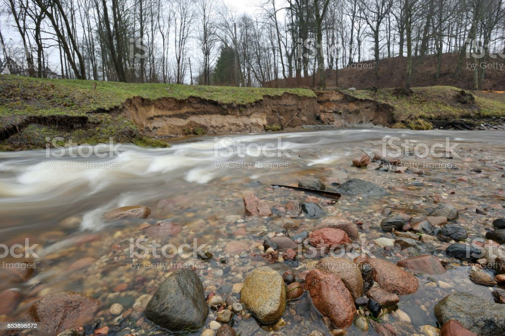 Natural erosion, shore of wild forest river stock photo