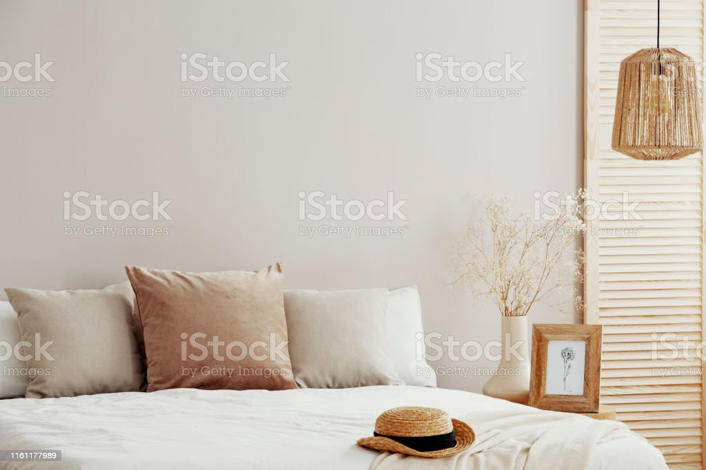 Natural fashionable bedroom interior with wicker hat on white bedding