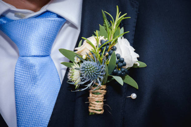 Natural flowers boutonniere in the pocket of the groom stock photo