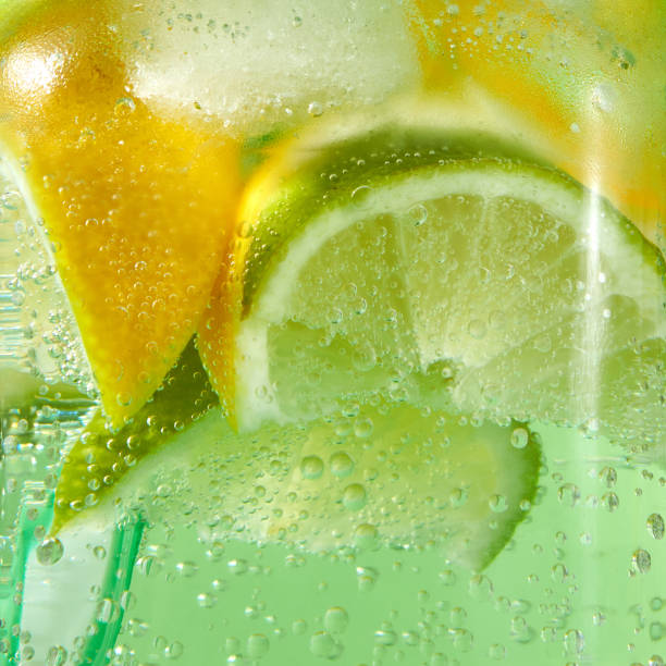 A natural fruit background with macro lime slices, lemon and a colored drinking plastic straw in a glass jar with aerated gassed bubbles. stock photo