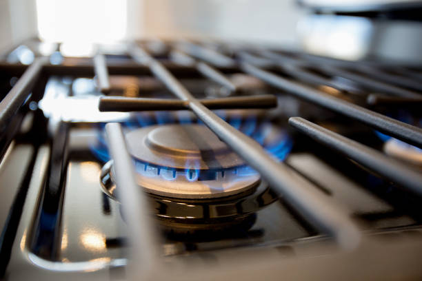 Natural Gas Blue Flame on a Domestic Cooking Range Stove Natural gas blue flame from a domestic gas stove in a new home. stove stock pictures, royalty-free photos & images
