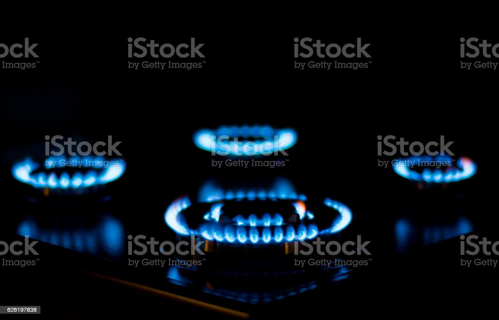 Natural gas burning a blue flames on black background stock photo