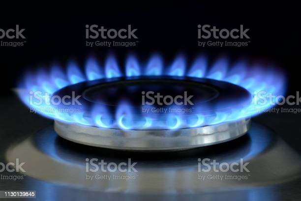 Photo of Natural gas burning on kitchen gas stove on black