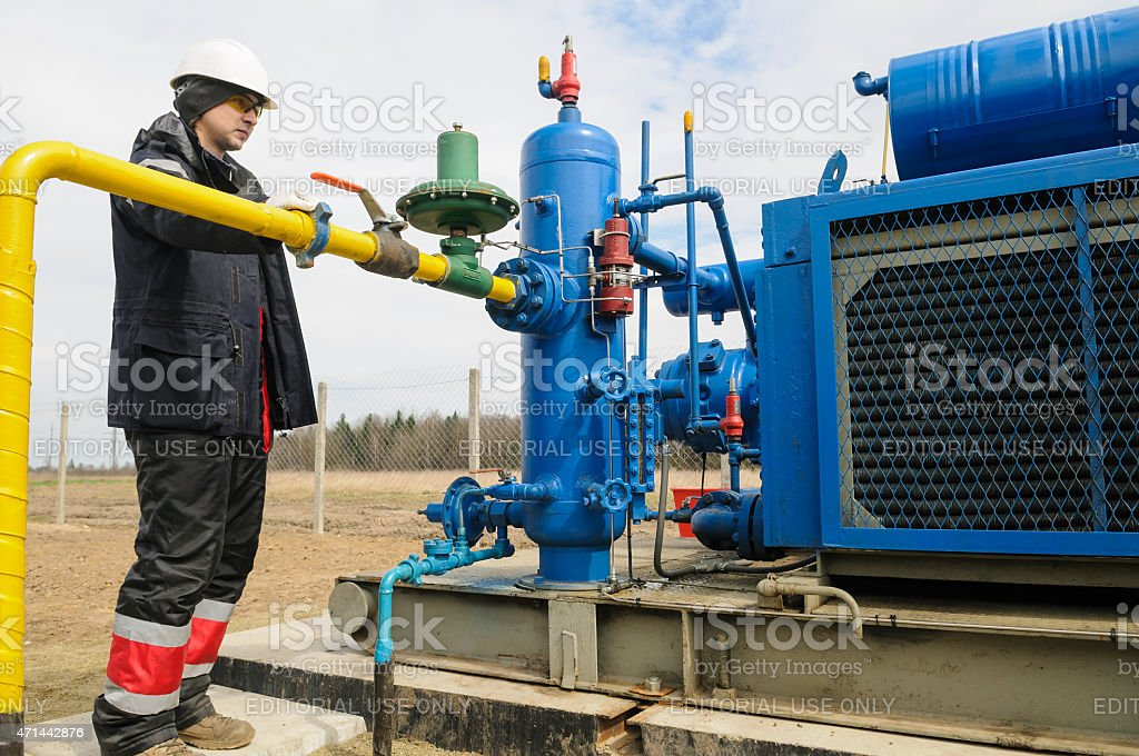 Worker employs equipment of the natural gas field station near...