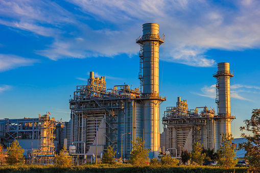 Natural gas fired turbine power plant with it's cooling towers rising into a cloud filled blue sky